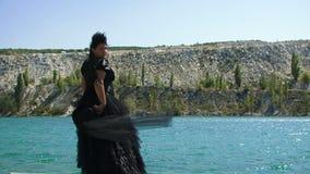 Meisje in een zwarte cilinder door het overzees Langzame Motie stock footage