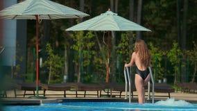 Meisje in een zwempak uit de pool stock videobeelden