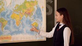 Meisje in eenvormige antwoorden van een Raad op de les van aardrijkskunde stock videobeelden
