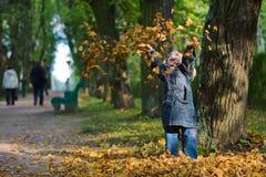 Meisje en bladeren bij de herfst Royalty-vrije Stock Fotografie