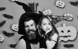 Meisje en gebaarde mens met gelukkige gezichten op groene achtergrond met decor Tovenaar en weinig heks in zwarte hoedenomhelzing Royalty-vrije Stock Foto's