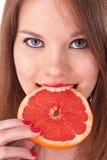 Meisje en grapefruit in haar tanden Royalty-vrije Stock Afbeelding