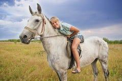 Meisje en grijs paard Stock Foto's
