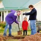 Meisje en haar grootouders die een boom planten stock fotografie