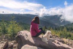 Meisje en haar hondzitting op een omhoog hoge rots Royalty-vrije Stock Afbeeldingen