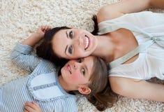 Meisje en haar moeder die op de vloer liggen Stock Foto
