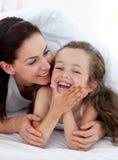 Meisje en haar moeder die pret op bed hebben Royalty-vrije Stock Foto