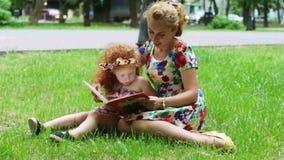 Meisje en haar moeder gelezen boek op gazon stock footage