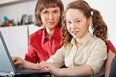 Meisje en haar moeder met laptop thuis stock foto's