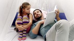 Meisje en haar vader die een boek samen lezen stock footage