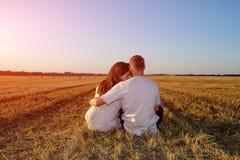 Meisje en haar vriend op een gebied van geoogste tarwe en het koesteren van zitting terug naar de camera royalty-vrije stock foto's