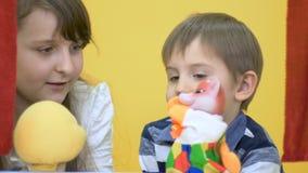 Meisje en het leuke jongen spelen met handspeelgoed in poppenspel stock footage