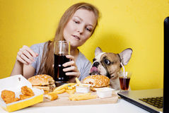 Meisje en hond die snel voedsel eten Stock Foto's