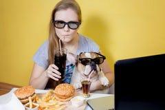 Meisje en hond die snel voedsel eten Stock Foto