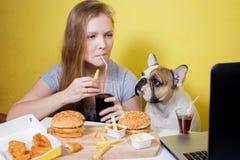 Meisje en hond die snel voedsel eten Royalty-vrije Stock Foto's