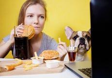 Meisje en hond die snel voedsel eten Stock Fotografie