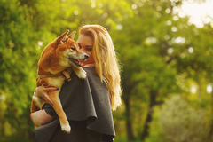 Meisje en hond het geknuffel van Shiba Inu stock afbeelding