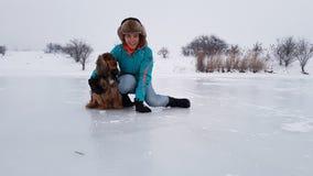 Meisje en hond op bevroren meer stock afbeelding