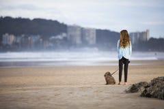Meisje en hond op zandig strand stock afbeeldingen