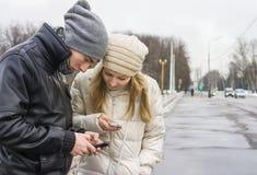 Meisje en jonge mens met telefoons Royalty-vrije Stock Fotografie