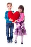 Meisje en jongen die een groot rood hart gevormd hoofdkussen houden Stock Afbeelding