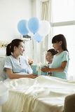 Meisje en jongen die hun moeder in het ziekenhuis bezoeken, die heden en ballons geven Stock Fotografie