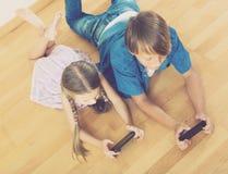 Meisje en jongen die in mobiele telefoons begraven Stock Afbeeldingen