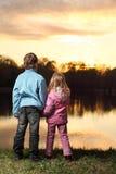 Meisje en jongen die op bank van rivier achteruitgaan Stock Fotografie