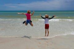 Meisje en jongen die op het strand springen Royalty-vrije Stock Afbeeldingen