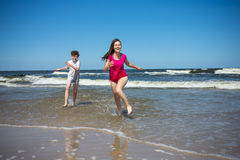 Meisje en jongen die op strand springen Royalty-vrije Stock Afbeelding