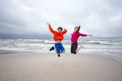 Meisje en jongen die op strand springen Stock Afbeelding