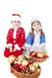 Meisje en jongen in Kerstmiskleren met speelgoed stock afbeelding