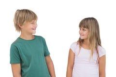 _meisje en jongen kijken bij elkaar en glimlachen Stock Afbeelding