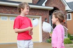 Meisje en jongen met gesponnen suiker Stock Afbeeldingen