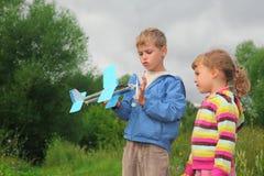 Meisje en jongen met stuk speelgoed vliegtuig in handen Stock Afbeeldingen