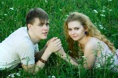 Meisje en jongen op het gras Stock Afbeeldingen