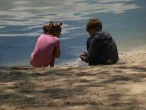 Meisje en jongen op rivierbank het spelen met zand en water stock afbeeldingen