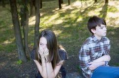 Meisje en jongens de Tienerjaren zitten terug naar elkaar Wrok, slechte verhouding royalty-vrije stock fotografie