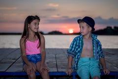 Meisje en jongens het spelen op het strand in zonsondergangtijd royalty-vrije stock afbeeldingen