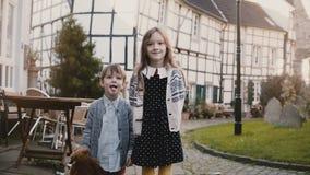 Meisje en jongenstribune die samen gezichten maken Europese siblings bekijken dwaas camera het glimlachen Helft-betimmerd huis 4K stock footage