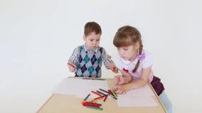 Meisje en jongensverf op document bladen met kleurpotloden stock footage