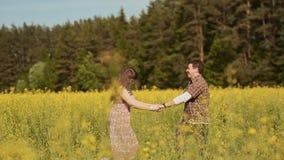 Meisje en Kerel die in het gele raapzaad gebied en lachen omcirkelen, die handen houden stock video