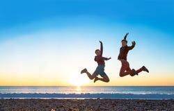 Meisje en Kerel die hoog met wapens omhoog spectaculaire zonsopgang bij oceaankust springen Stock Afbeelding