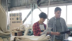 Meisje en kerel die in houten de tablet en het document van de workshop sprekende holding documenten lopen stock videobeelden