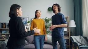 Meisje en kerel die nieuwe flat bespreken met makelaar in onroerend goed die binnen spreken stock videobeelden