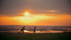 Meisje en kerel speelbadminton op het gebied, die zich naast hun kleine zoon, de avond van de zonsondergangzomer bevinden stock video