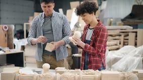 Meisje en kerelarbeiders die houten dingen in en workshop oppoetsen die spreken glimlachen stock videobeelden