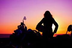 Meisje en klassieke motorfiets bij zonsondergang stock fotografie
