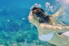 Meisje en kleine vissen die onderwaterportret zwemmen Van het overzeese achtergrond de zomer de blauwe water met bellen Royalty-vrije Stock Foto