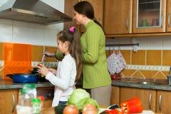 Meisje en mamma met braadpan stock foto